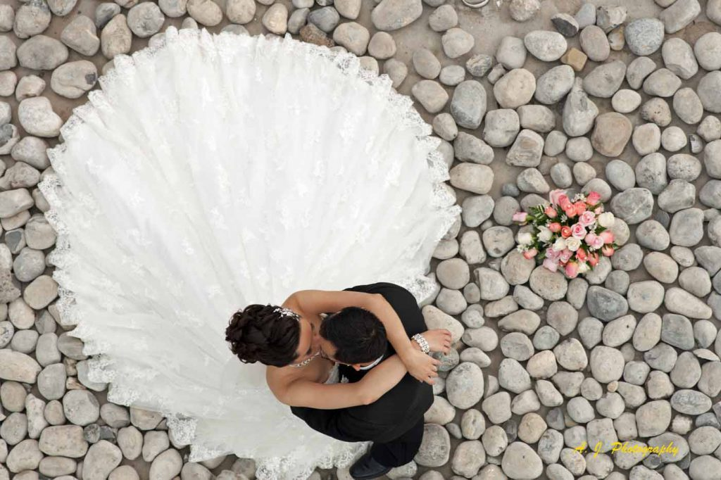 Bride and groom embracing with flowers in a rock garden
