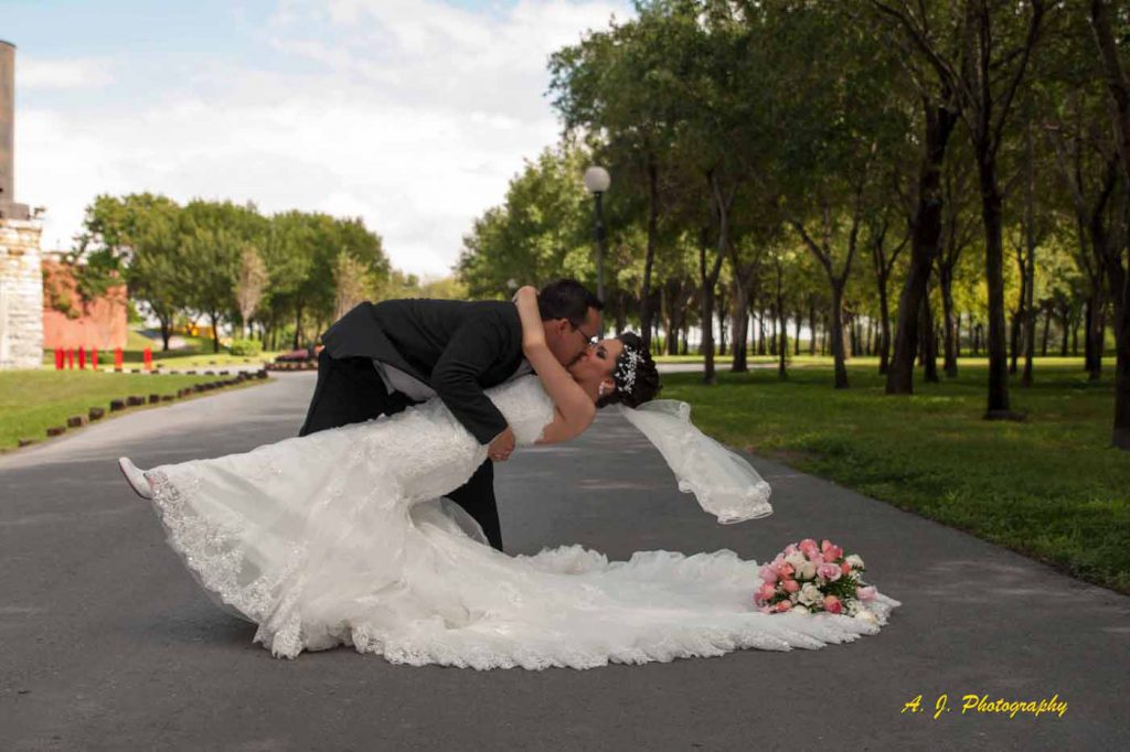 Bride and groom kissing in a park
