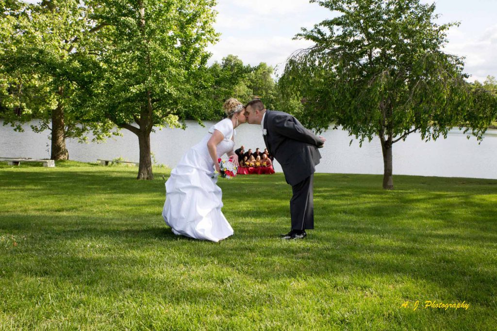 Bride and groom kissing with wedding party watching