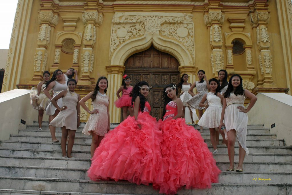 Two quinceañeras and their maids