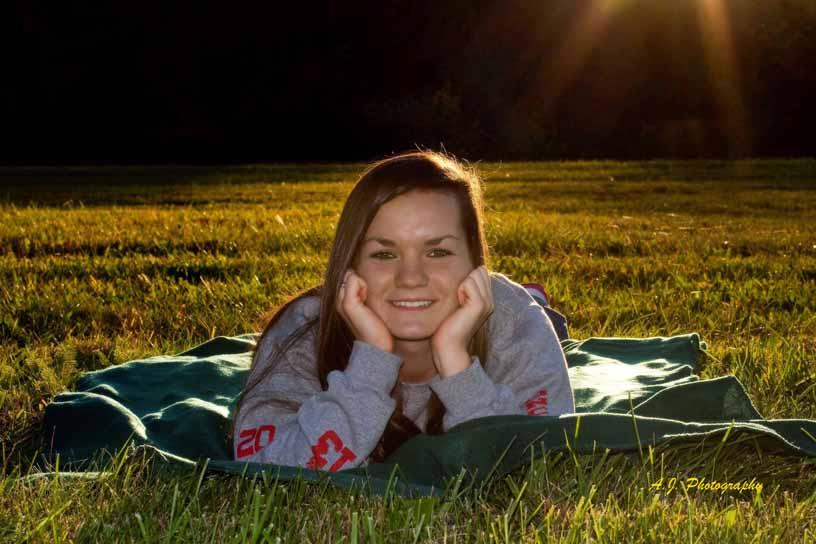 Senior girl lying on the grass at sunset