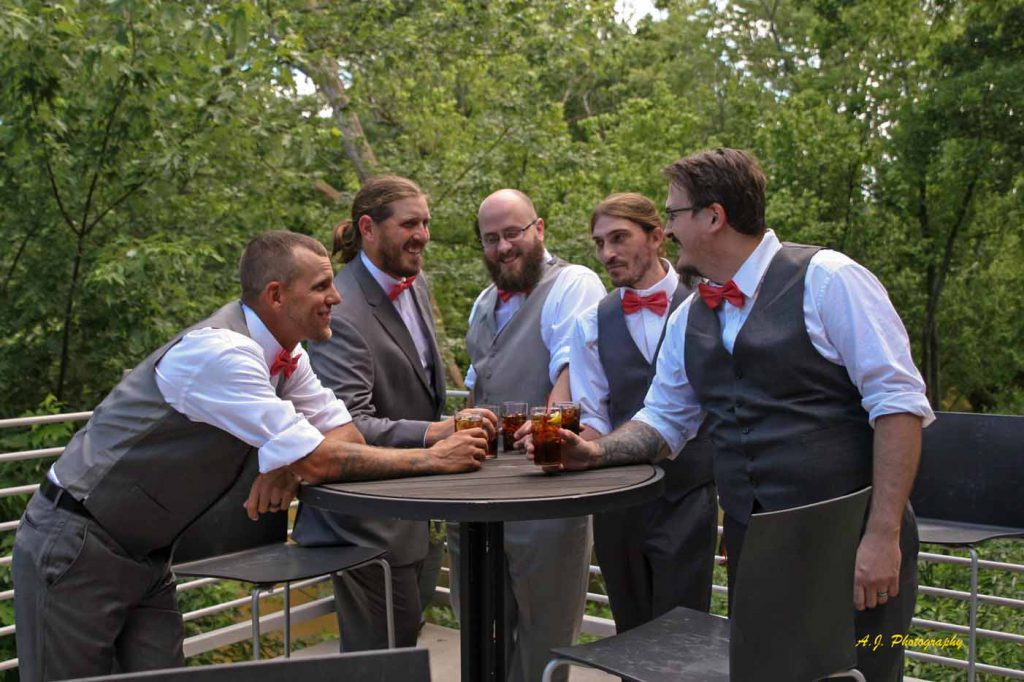 Groom and his groomsmen having a drink together before the wedding